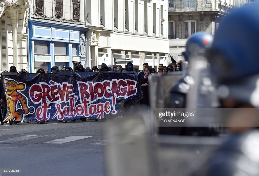 People take part in a protest against the government's planned labour law reforms in Nantes, western France, on May 3, 2016. High school pupils and workers protested against deeply unpopular labour reforms that have divided the Socialist government and raised hackles in a country accustomed to iron-clad job security. / AFP / LOIC