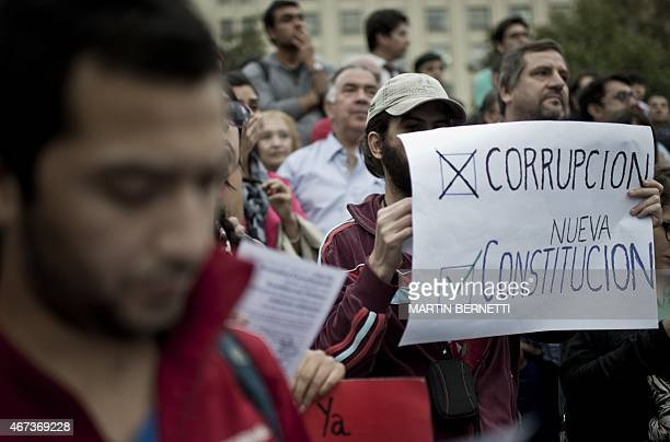 People take part in a protest called by social movements against corruption in front of La Moneda Presidential Palace in Santiago on March 23 2015...