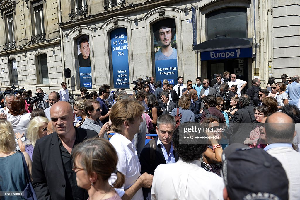 People take part in a rally in front of Europe 1 radio station studio in Paris on July 9, 2013 in support of the two French radio journalists Didier Francois and Edouard Elias who have been kidnapped in Syria.