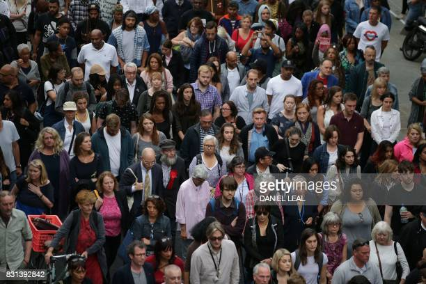People take part in a silent march in memory of the victims of the Grenfell Tower fire in west London on August 14 2017 The march marks two months...