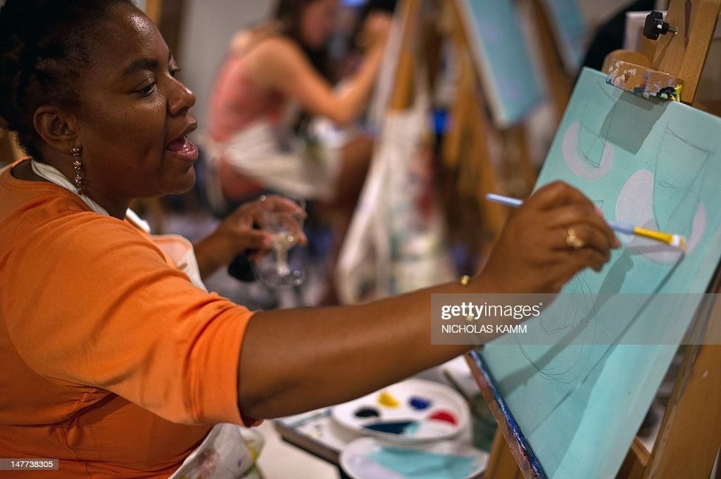 People take part in a 'Sippin' and Paintin'' event at Living Social in Washington on June 26, 2012. Online coupons are last year's news.That is the view from number two US online deals firm Living Social, which is battling sector leader Groupon by offering what excutives call 'unique' or original experiences that are not simply linked to discounts. AFP PHOTO/Nicholas KAMM