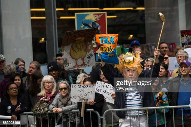 People take part in a Tax Day protest on April 15 2017 in New York City Thousands of activists march to Trump Tower to demand that President Donald...