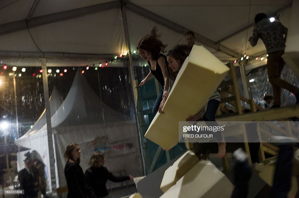 People take part in an art installation by artist Danish Palle Nielsen, on October 5, 2013, at Stalingrad Square in Paris, during Paris' Nuit Blanche (White Night) event.