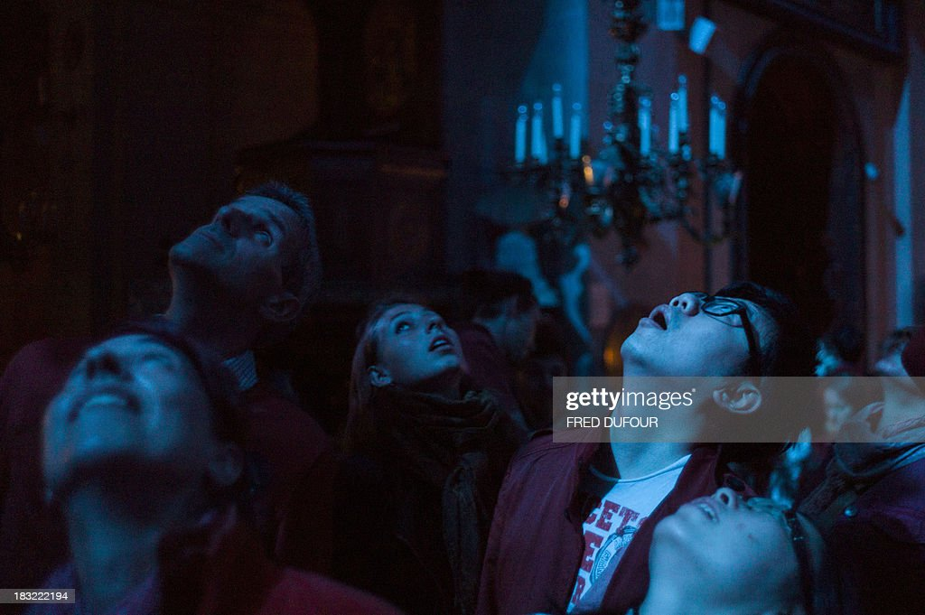 People take part in an art installation by artist Dominique Lacloche, on October 5, 2013, at the Saint-Paul-Saint-Louis church in Paris, during Paris' Nuit Blanche (White Night) event. AFP PHOTO / FRED DUFOUR