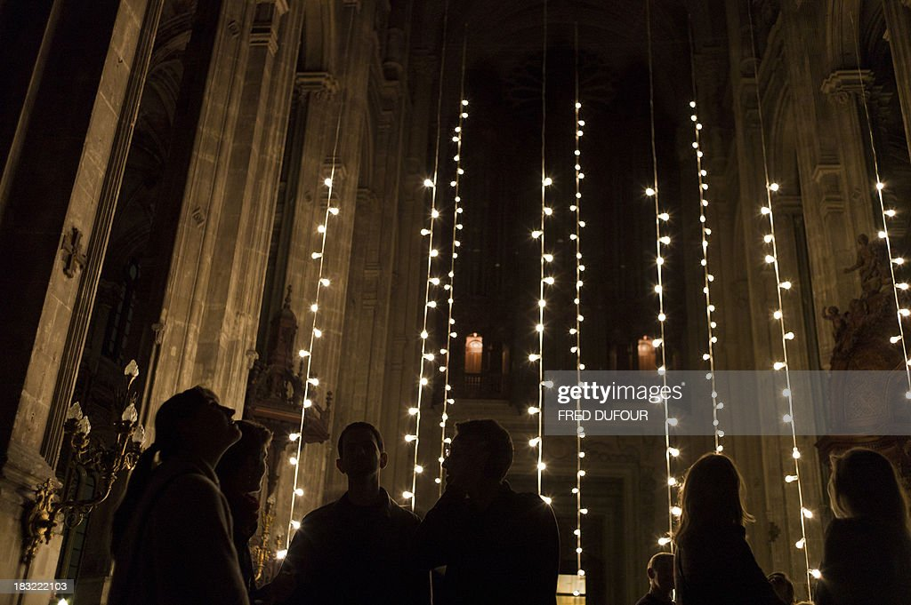 People take part in an art installation by artist Felix Gonzales-Torres, on October 5, 2013, at the Saint Eustache church in Paris, during Paris' Nuit Blanche (White Night) event.