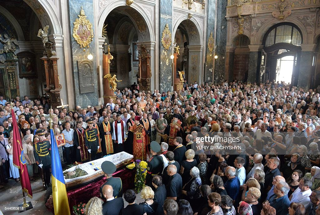 People take part in n funeral ceremony with Wassyl Slipak in St. Paul and Peter Cathedral in the western Ukrainian city of Lviv on July 1, 2016. A Ukrainian opera singer who performed for two decades in France before joining Kiev's volunteer forces fighting pro-Russian insurgents has been killed in the separatist east, officials said on June 29. Wassyl Slipak, a baritone who was born in 1974, left France and joined the armed wing of Ukraine's ultranationalist Pravy Sektor (Right Sector) party shortly after a war that has claimed more than 9,440 lives broke out in April 2014, according to his website. Slipak originally performed at the Lviv Conservatory in western Ukraine before passing an entrance exam at the prestigious Paris Opera and launching his career in France. / AFP / Yuriy Dyachyshyn