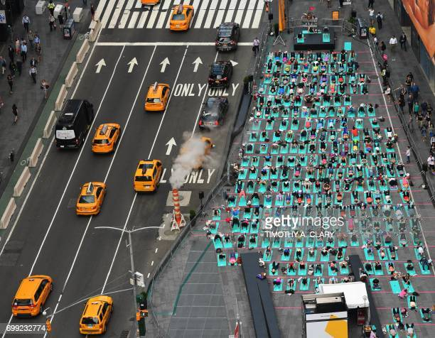 TOPSHOT People take part in the 15th annual Times Square yoga event celebrating the Summer Solstice the longest day of the year during classes in the...