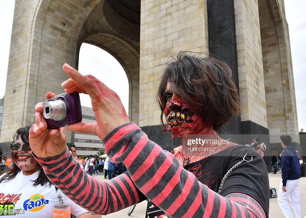 People take part in the annual 'Zombie Walk' at the Revolution Square in Mexico City on October 22, 2016. / AFP / YURI