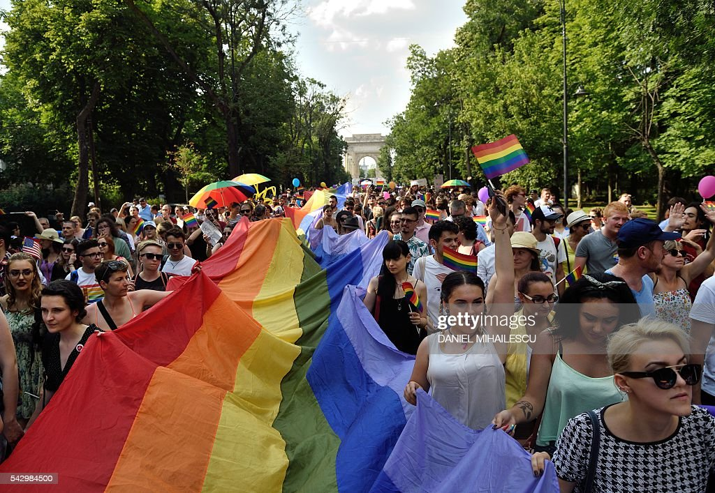 People take part in the Bucharest Pride, an event celebrating diversity and LGBT community in Bucharest on June 25, 2016. / AFP / DANIEL