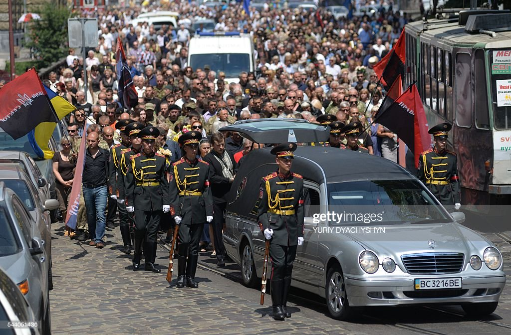 People take part in the funeral ceremony of Wassyl Slipak in St. Paul and Peter Cathedral in the western Ukrainian city of Lviv on July 1, 2016. A Ukrainian opera singer who performed for two decades in France before joining Kiev's volunteer forces fighting pro-Russian insurgents has been killed in the separatist east, officials said on June 29. Wassyl Slipak, a baritone who was born in 1974, left France and joined the armed wing of Ukraine's ultranationalist Pravy Sektor (Right Sector) party shortly after a war that has claimed more than 9,440 lives broke out in April 2014, according to his website. Slipak originally performed at the Lviv Conservatory in western Ukraine before passing an entrance exam at the prestigious Paris Opera and launching his career in France. / AFP / Yuriy Dyachyshyn