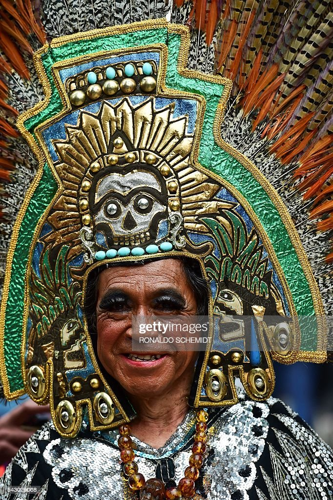 People take part in the Gay Pride Parade in Mexico City, on June 25, 2016. Thousands of people took to the streets in the Mexican capital to participate in the parade. / AFP / RONALDO