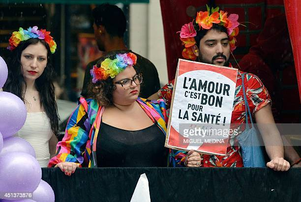 People take part in the lesbian gay bisexual and transgender visibility march the Gay Pride under the rain on June 28 2014 in Paris The placard reads...