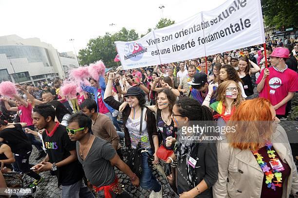 People take part in the lesbian gay bisexual and transgender visibility march the Gay Pride under the rain on June 28 2014 in Paris The banner reads...
