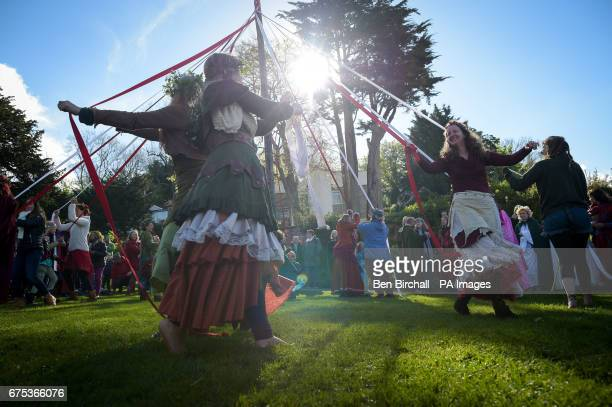 People take part in the traditional maypole dance at the Chalice Well Glastonbury where Beltane festivities are taking place on May Day