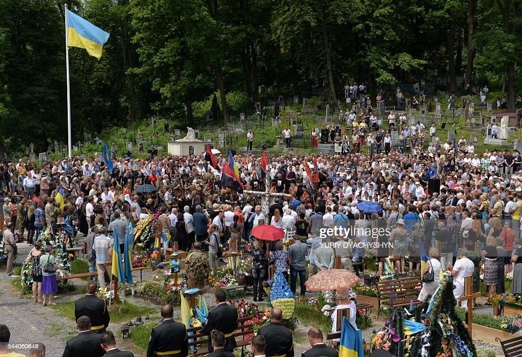 People take part in thr funeral ceremony of Wassyl Slipak in St. Paul and Peter Cathedral in the western Ukrainian city of Lviv on July 1, 2016. A Ukrainian opera singer who performed for two decades in France before joining Kiev's volunteer forces fighting pro-Russian insurgents has been killed in the separatist east, officials said on June 29. Wassyl Slipak, a baritone who was born in 1974, left France and joined the armed wing of Ukraine's ultranationalist Pravy Sektor (Right Sector) party shortly after a war that has claimed more than 9,440 lives broke out in April 2014, according to his website. Slipak originally performed at the Lviv Conservatory in western Ukraine before passing an entrance exam at the prestigious Paris Opera and launching his career in France. / AFP / Yuriy Dyachyshyn