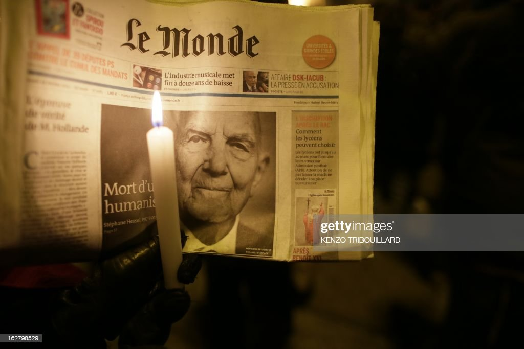 People take part on February 27, 2013 in Paris, in a rally to pay homage to French resistance hero and Holocaust survivor Stephane Hessel who has died today at the age of 95. The career diplomat was already celebrated as one of the last living heroes of the 20th century when, as a nonagenarian, he became the unlikely godfather of youth protest movements such as 'Occupy Wall Street' and Spain's 'Indignados'. AFP PHOTO KENZO TRIBOUILLARD
