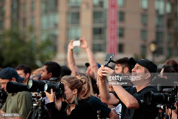 People take photographs as they view the 'Manhattanhenge' sunset from Hunters Point South Park July 11 2016 in the Queens borough of New York City...