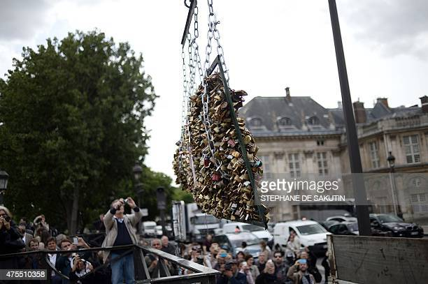 People take photographs as workers remove panels bearing 'love padlocks' attached on the railings of the Pont des Arts bridge in Paris on June 1 2015...