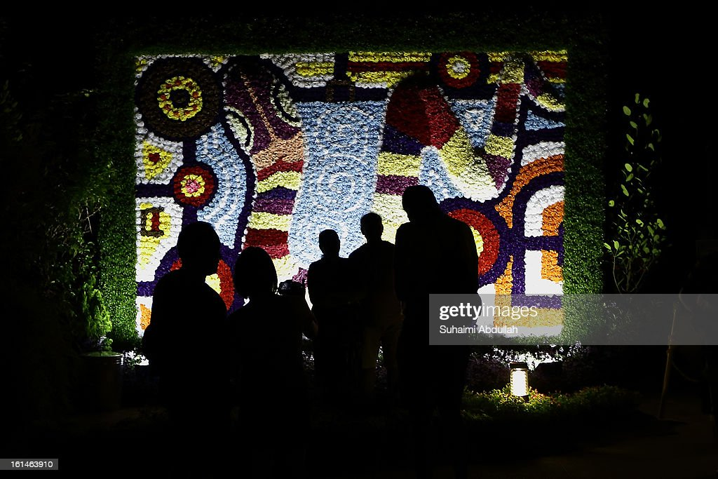 People take photographs in front of a giant snake-themed floral display at the Sentosa Flowers exhibition at Palawan Beach on February 11, 2013 in Singapore. Millions of spring flowers decorate the island in celebration of the Chinese New Year, the year of the Snake.