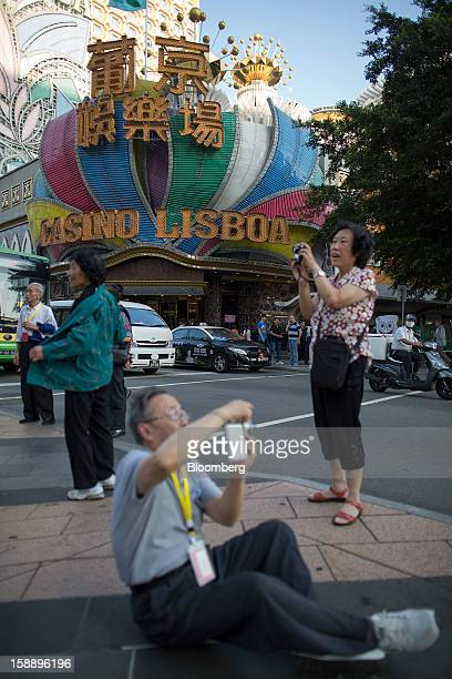 People take photographs in front of the Casino Lisboa operated by SJM Holdings Ltd in Macau China on Wednesday Oct 24 2012 Las Vegas Sands Corp Wynn...