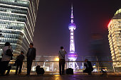 People take photographs in front of the Oriental Pearl Radio TV Tower center in the Lujiazui district of Shanghai China on Friday April 24 2015 Yuan...