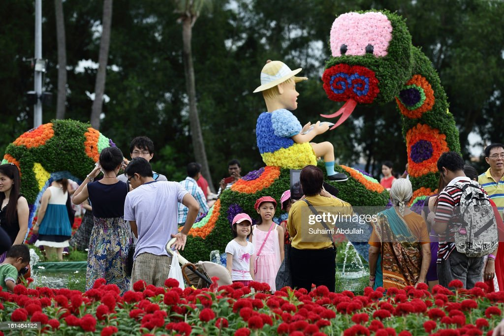 People take photographs of a flower exhibit in the shape of a zodiac water snake at the Sentosa Flowers exhibition at Palawan Beach on February 11, 2013 in Singapore. Millions of spring flowers decorate the island in celebration of the Chinese New Year, the year of the Snake.