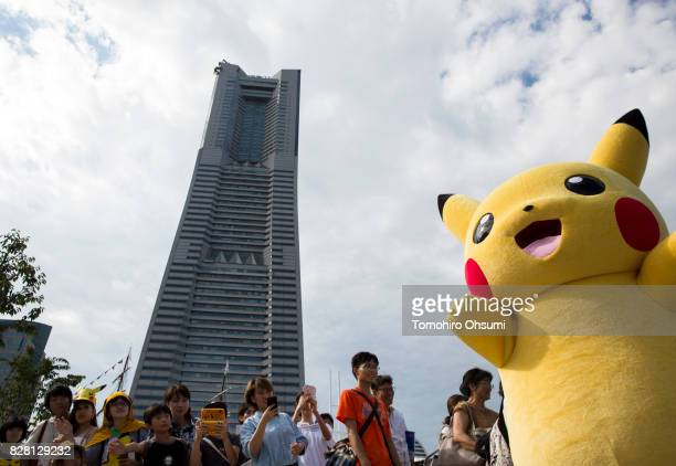 People take photographs of a performer dressed as Pikachu a character from Pokemon series game titles during the Pikachu Outbreak event hosted by The...