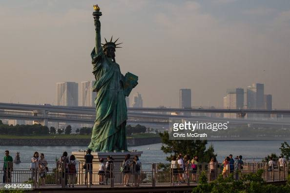 People take photographs of a replica of the Statue of Liberty at the Odaiba shoreline on May 31 2014 in Tokyo Japan Odaiba is a large artificial...