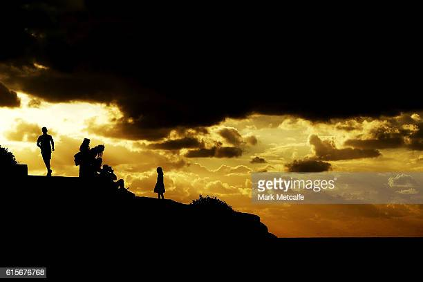 People take photographs of a Sculpture as a jogger runs by at Sculpture By The Sea at Tamarama on October 20 2016 in Sydney Australia