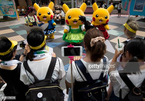 People take photographs of performers dressed as Pikachu a character from Pokemon series game titles during the Pikachu Outbreak event hosted by The...