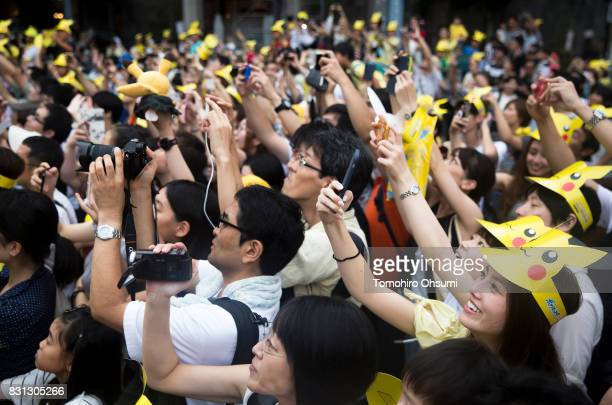 People take photographs of performers dressed as Pikachu a character from Pokemon series game titles during a parade as part of the Pikachu Outbreak...