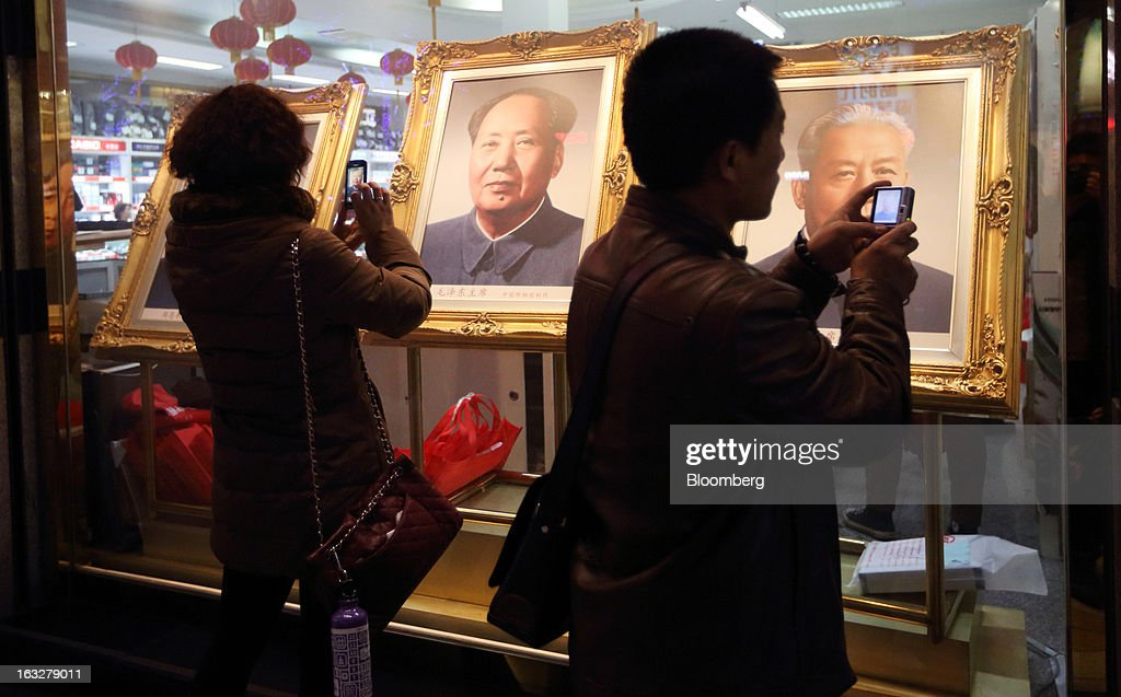 People take photographs of portraits of former Chinese leaders Zhou Enlai, from left, Mao Zedong and Liu Shaoqi displayed at a shop at night in Beijing, China, on Wednesday, March 6, 2013. China maintained its economic-growth target at 7.5 percent for 2013 while setting a lower inflation goal of 3.5 percent, setting up a challenge for new leaders to keep prices in check without harming expansion. Photographer: Tomohiro Ohsumi/Bloomberg via Getty Images