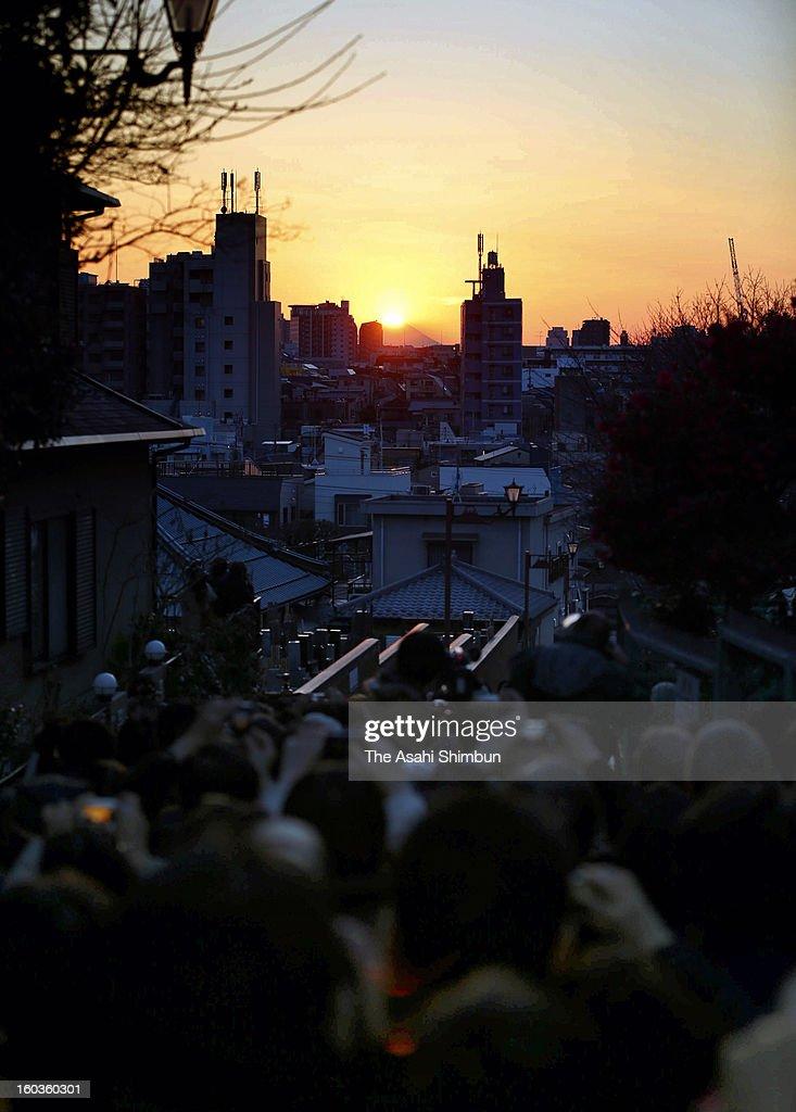 People take photographs of so-called 'Diamond Fuji', the sunset on the summit of Mount Fuji, at Nippori Fujimi-zaka on Janaury 29, 2013 in Tokyo, Japan.