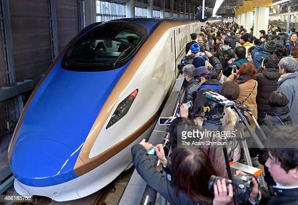 People take photographs of the new Hokuriku Shinkansen arriving at Kanazawa Station on March 14 2015 in Kanazawa Ishikawa Japan A string of...