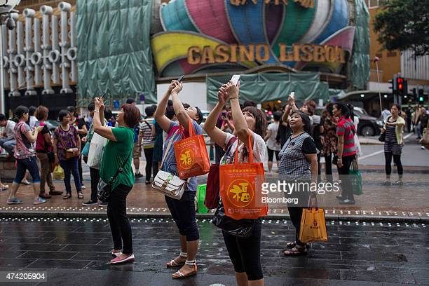 People take photographs with mobile phones outside the Casino Grand Lisboa operated by SJM Holdings Ltd in Macau China on Wednesday May 20 2015...