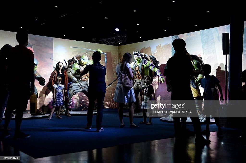 People take photographs with Teenage Mutant Ninja Turtles figures at Bangkok Comic Con in Bangkok on April 29, 2016. / AFP / LILLIAN