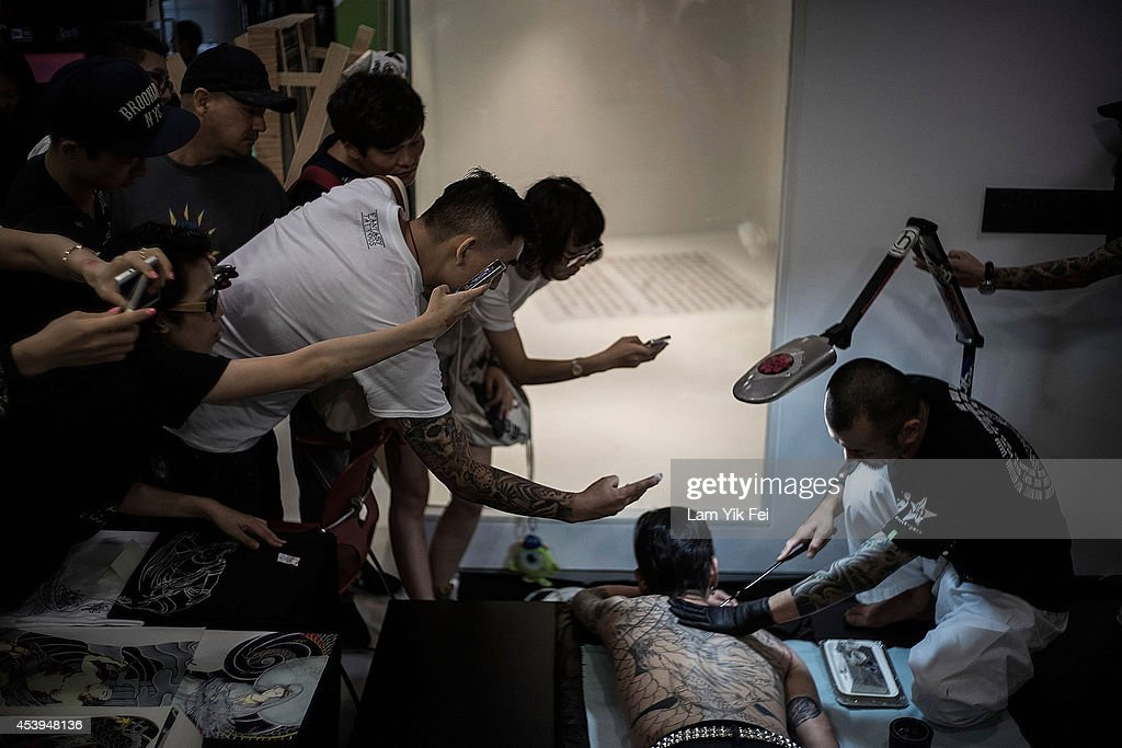 People take photos and watch as a man gets a tattoo at the Hong Kong Tattoo Convention on August 22, 2014. in Hong Kong. The 2nd International Hong Kong Tattoo Convention 2014 features tattoo artists from around the world.
