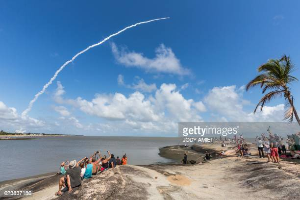 TOPSHOT People take photos as an Ariane 5 space rocket with a payload of four Galileo satellites lifts off from ESA's European Spaceport in Kourou...