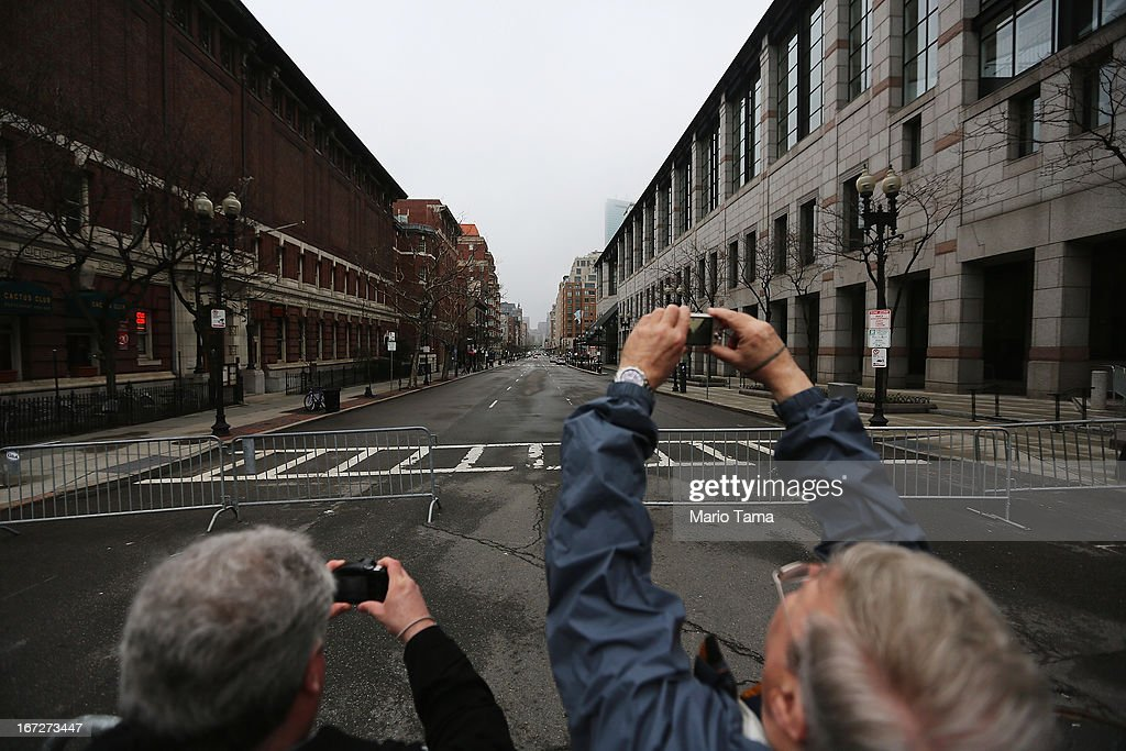 People take photos at a barricade blocking a still closed section of Boylston Street near the site of the Boston Marathon bombings on April 23, 2013 in Boston, Massachusetts. Business owners and residents of the closed section were allowed to return to their properties today while under escort of city staff.