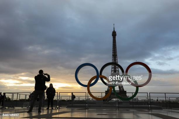 People take photos at sunrise by the Olympic rings installed on the Esplanade du Trocadero near the Eiffel tower following the Paris' nomination as...