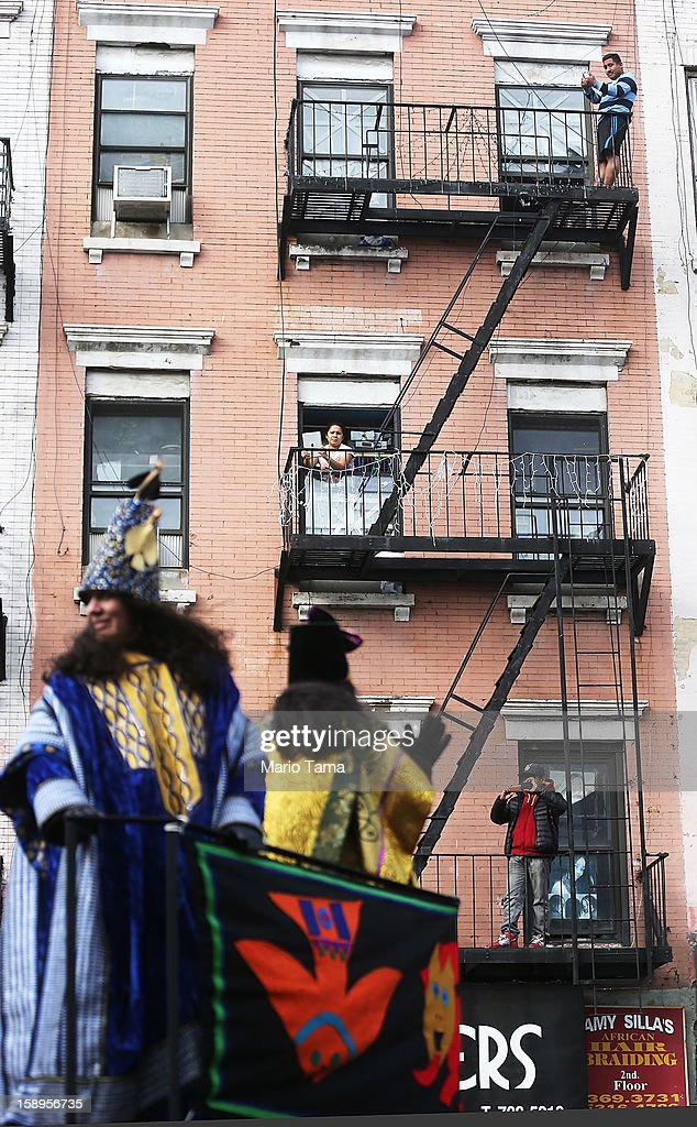 People take photos from a fire escape as revelers pass during the Three Kings Day Parade in East Harlem on January 4, 2013 in New York City. The parade celebrates the Feast of the Epiphany, also known as Three Kings Day, marking the Biblical story of the visit of three kings to Bethlehem to visit the baby Jesus, revealing his divinity.