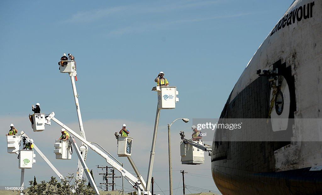 People take photos from cherry pickers as NASA Space Shuttle Endeavour moves on Crenshaw Drive enroute to the California Science Center on October 13, 2012 in Inglewood, California. Endeavour is on its last mission - a 12-mile creep through city streets, past an eclectic mix of strip malls, mom-and-pop shops, tidy lawns and faded apartment buildings. Its final destination is the California Science Center in South Los Angeles where it will be put on display. NASA's Space Shuttle Program ended in 2011 after 30 years and 135 missions.