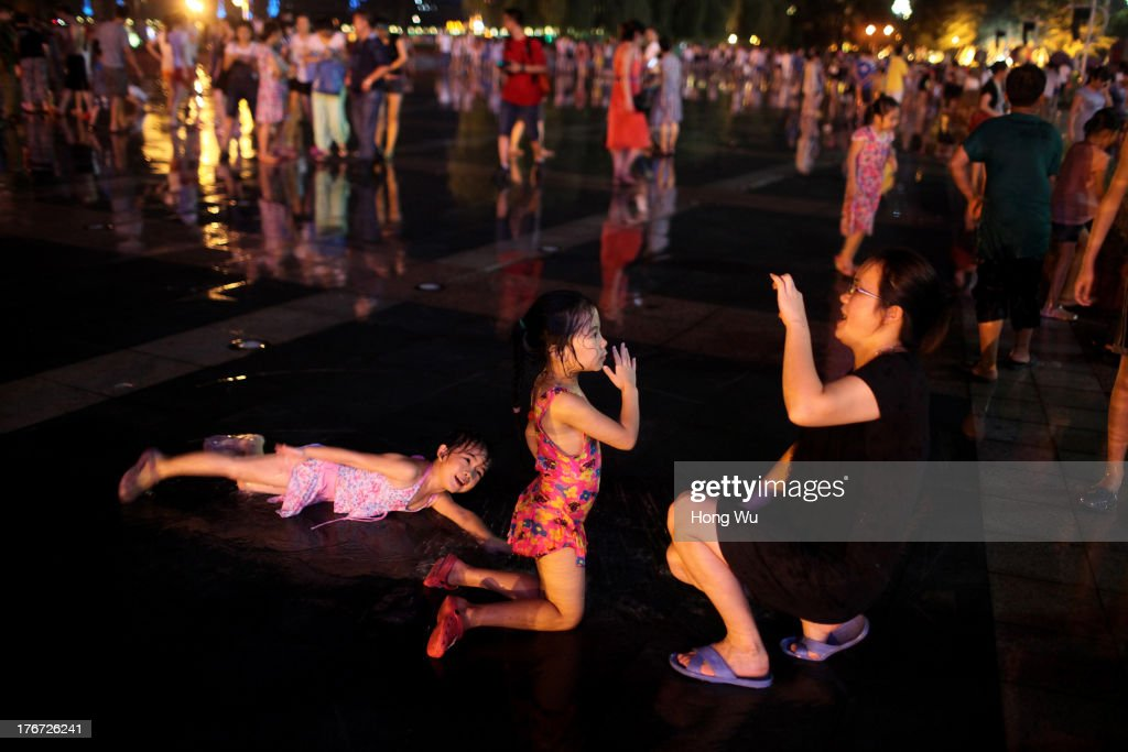 People take photos in a fountain square on August 4, 2013 in Chongqing, China. Chongqing is a major city in southwest China and became the municipality was created on 14 March 1997. It known as a 'Mountain City' and 'River City' was constructed on the mountain and along the Yangtze River.