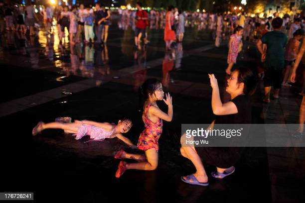 People take photos in a fountain square on August 4 2013 in Chongqing China Chongqing is a major city in southwest China and became the municipality...