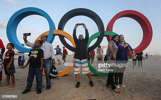 People take photos in front of a set of Olympic rings created from recycled material on Copacabana beach one of the Olympic venues on July 23 2016 in...