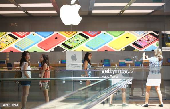 People take photos in front of Brazil's first Apple retail store in the Village Mall shopping center on February 13 2014 in Rio de Janeiro Brazil The...