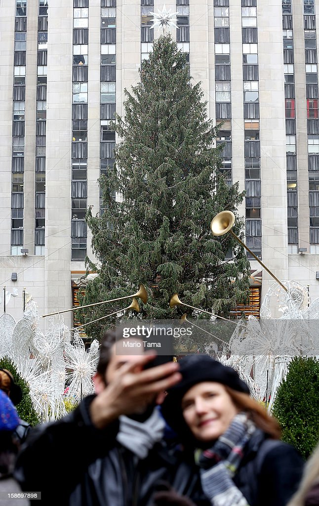 People take photos near the Christmas tree at Rockefeller Center on Christmas Eve on December 24, 2012 in New York City. Christians around the world are gearing up for Christmas festivities on December 25.