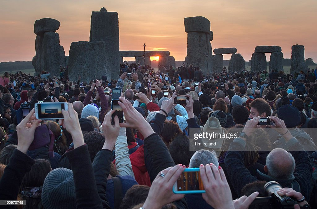 People take photos of the Summer Solstice sunrise at Stonehenge on June 21, 2014 in Wiltshire, England. A sunny forecast brought thousands of revellers to the 5,000 year old stone circle in Wiltshire to see the sunrise on the Summer Solstice dawn. The solstice sunrise marks the longest day of the year in the Northern Hemisphere.