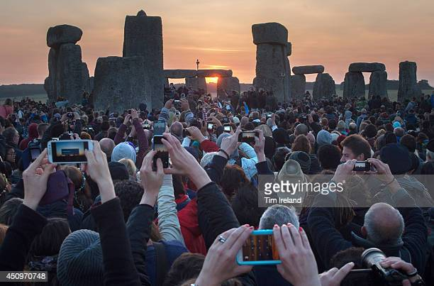 People take photos of the Summer Solstice sunrise at Stonehenge on June 21 2014 in Wiltshire England A sunny forecast brought thousands of revellers...