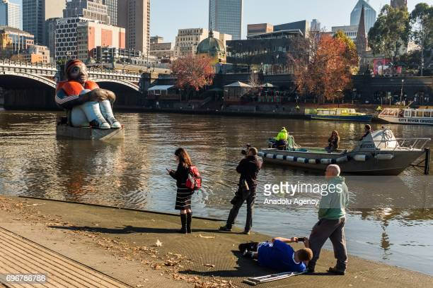 People take photos of the travelling artwork titled 'Inflatable Refugee' on the Yarra River on June 17 2017 in Melbourne Australia The five metrehigh...